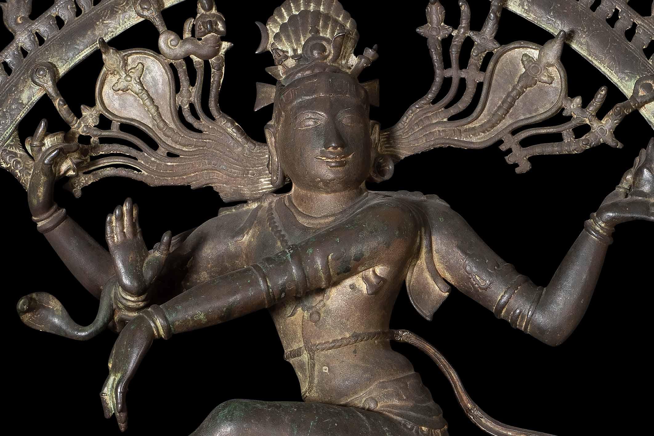 Een bronzen beeld dat een dansende Shiva voorstelt. Het beeld staat centraal in een vlammenkrans, met één been van de grond. Het andere been rust op een figuur die een dwerg voorstelt. Shiva, voorgesteld met vier armen, houdt een kleine trommel en een vlam vast.