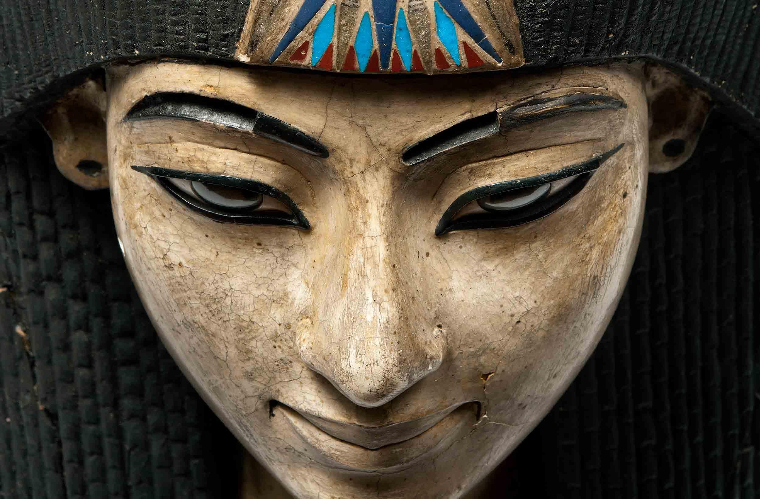 Een Egyptisch dodenmasker gemaakt uit linnen en beschilderd stuc op linnen. Een geïdealiseerd gelaat met zwarte haartooi en gemaquilleerde ogen. Rond de hals gouden sierraden met blauwe, rode en groene versiering.