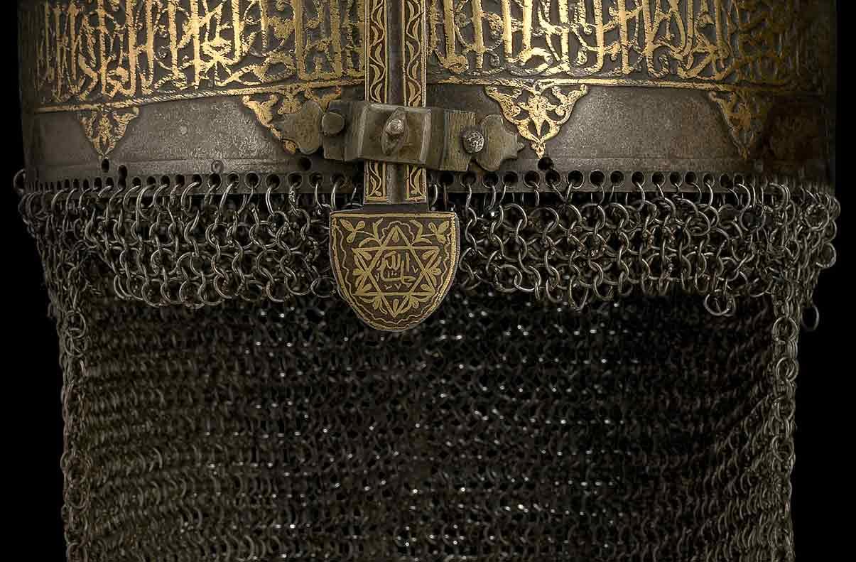 Een stalen helm, rijk versierd met gouden oud arabisch Thuluth schrift en arabesken. De helm draagt maliën als nekbescherming en heeft een beweegbare neusbeschermer uit staal.