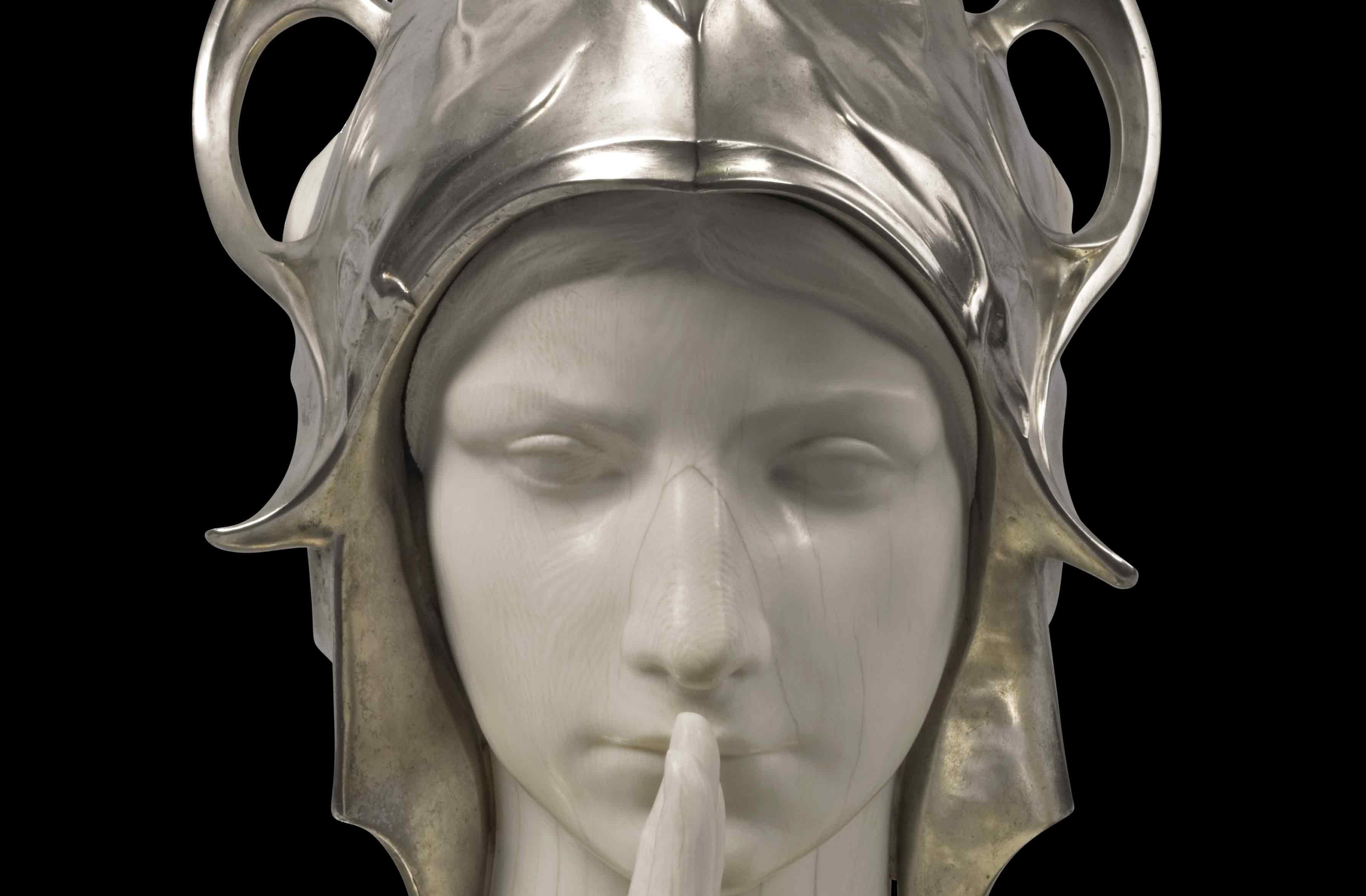 Een buste van een vrouw, gemaakt uit ivoor. De vrouw heft haar rechterhand en houdt deze gestrekt voor de mond. Ze draagt een harnas en helm uit zilver. De helm is versierd met een adelaarskop en adelaarsvleugels en planten motieven. Ook het harnas is versierd met plantenmotieven. Rond de pols van de vrouw slingert zich een slang.